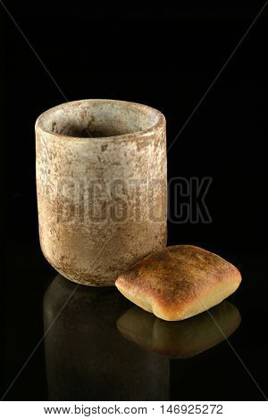 Cup of wine and bread as symbols of Communion over dark background