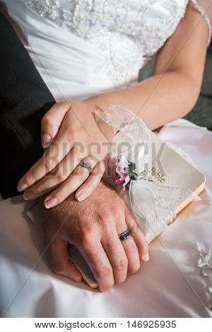 Newly married bride and groom place hands together with rings and bible, religious wedding