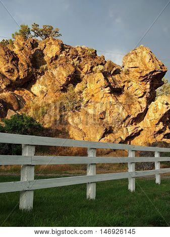 A storm lit rock outcropping borders a Central Oregon farm.