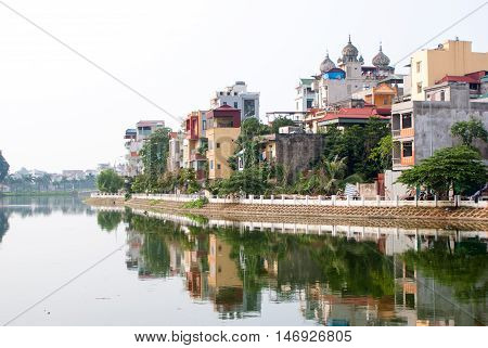 Ladnscape Of Hanoi With Buildings Reflected In The River