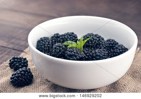 Close Up Of Ripe Blackberries In A White Ceramic Bowl Over Rustic Wooden Background