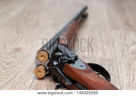 A wooden retro shotgun with shotgun shells on wooden background