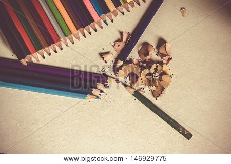 Colored pencils angle / Many different colored pencils on cement background / sharpened pencil with shavings