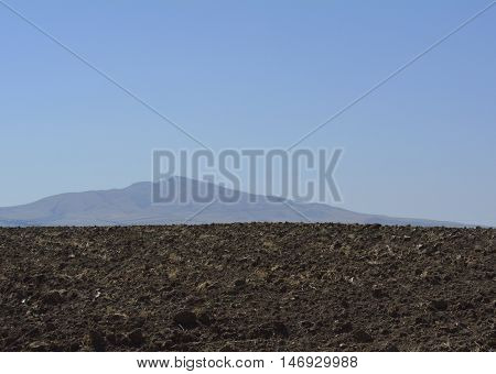 plowed field and the mountains on the horizon