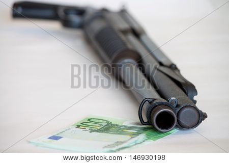Close up of black weapon laying on heap of hundred dollar bills