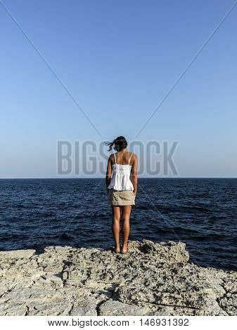 girl admiring the deep blue sea by the riff