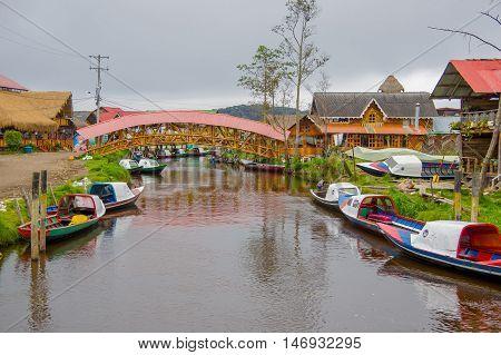 PASTO, COLOMBIA - JULY 3, 2016: nice wood bridge standing over the river close to la cocha lake