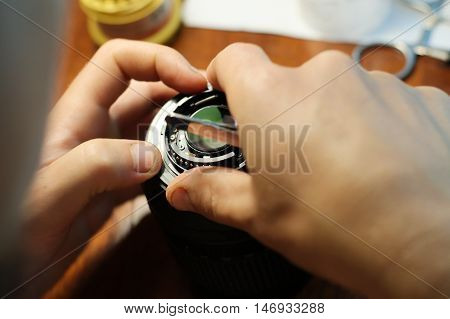 Engineer repairing objective camera lens in raw workplace