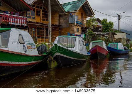 PASTO, COLOMBIA - JULY 3, 2016: some colorfull boats parked next to a shore and some houses in la cocha lake.