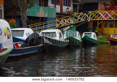 PASTO, COLOMBIA - JULY 3, 2016: some colorfull boats parked on the shore next to some houses and under a small bridge in la cocha lake