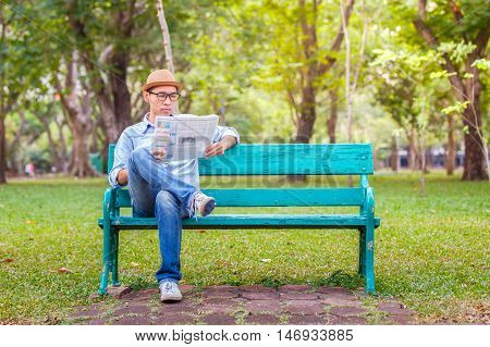 Asian young Man with hat sitting on a wooden bench and reading a newspaper in a park