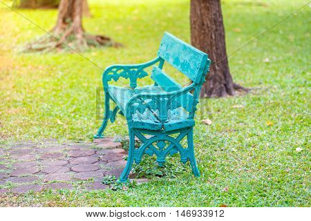 Wooden bench in a green park with trees