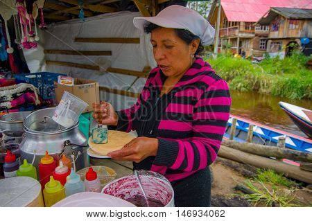 PASTO, COLOMBIA - JULY 3, 2016: unidentified woman adding some caramel to a wafer in a location close to la cocha lake.