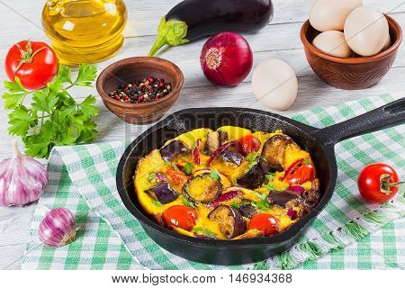 scrambled eggs eggplant onion and tomato in frying pan on kitchen towel garlic aubergineegg olive oil parsley and ripe tomatoes on wooden boards view from above close-up