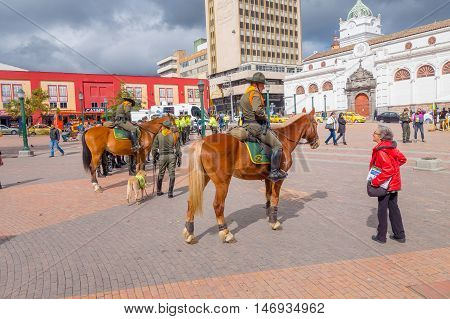 PASTO, COLOMBIA - JULY 3, 2016: police officer mounted on a horse talking on the center square of the city.