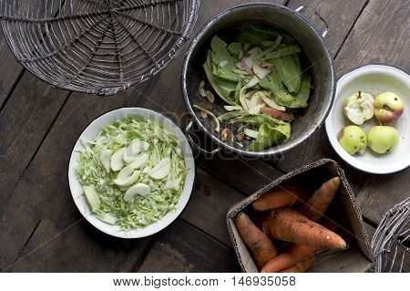 Peeling and chopping various fresh vegetables on the floor of a kitchen overhead shot