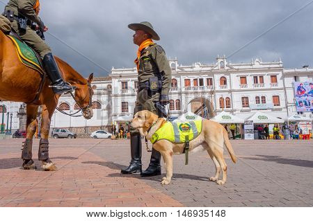 PASTO, COLOMBIA - JULY 3, 2016: unidentified policeman standing on the central square with a policedog.