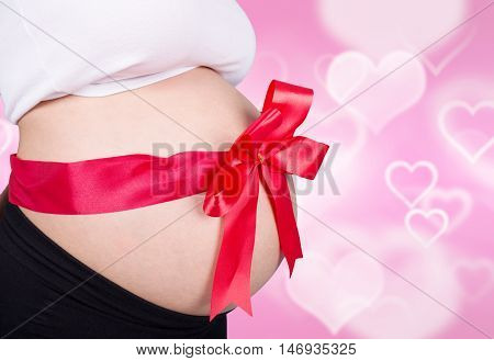 Close Up Pregnant Woman With Red Ribbon Gift On Belly On Heart Backrground