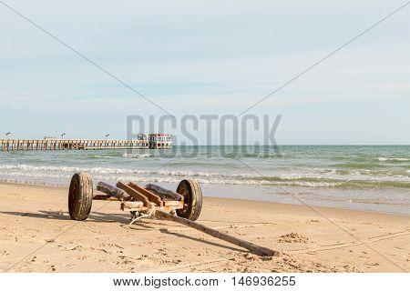 wooden boat trailer for transportation on beach near fishing jetty .