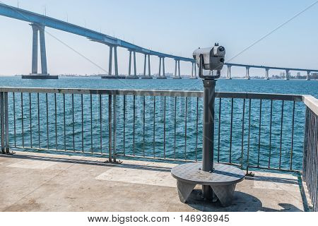 Sightseeing binoculars on the Cesar Chavez Park pier with the San Diego Bay and the Coronado Bridge.