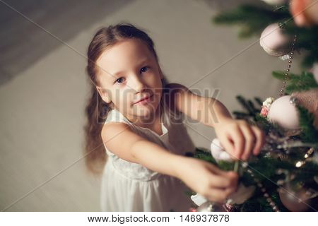 Little girl decorating christmas tree, top view, vintage toned