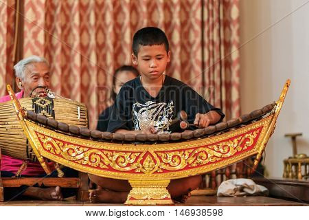 RATCHABURI THAILAND - MARCH 20 2016: Unidentified boy playing xylophone on the stage of Wat Khanon Thailand. Wooden xylophone called ranat is most prominent instrument in classical Thai music.
