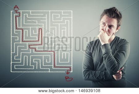 Thoughful man is considering how to shorten the path through the maze point a to the point b .