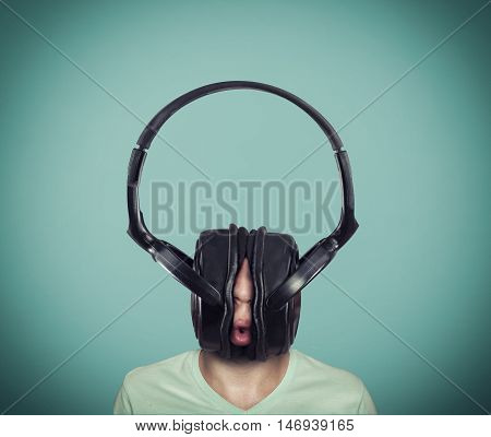 Man listening music on huge headphones .