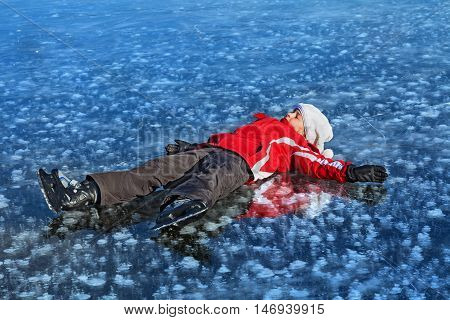 Young girl with ice skates resting on the frozen lake surface in the bright sunshine - copy space