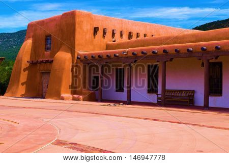 Building with adobe style architecture and mountains beyond taken in Santa Fe, NM poster