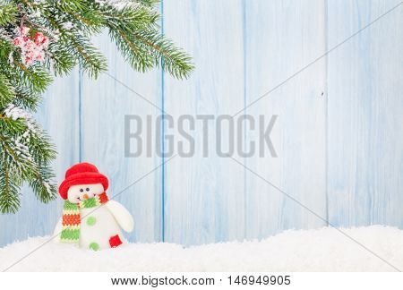 Christmas snowman toy and fir tree branch in snow. View with copy space