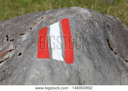White and red trail sign painted on a Rock. Lech Valley. Austria