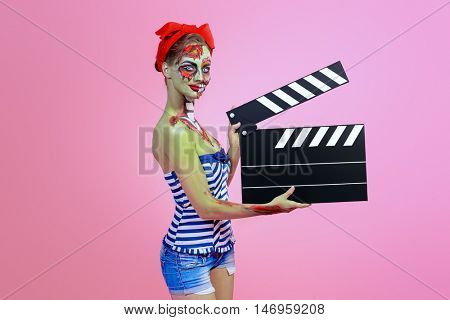 Pin-up zombie woman holding clapperboard over pink background. Body-painting project. Glamorous zombie girl. Halloween make-up.