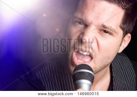 Singing man in spotlight with microphone