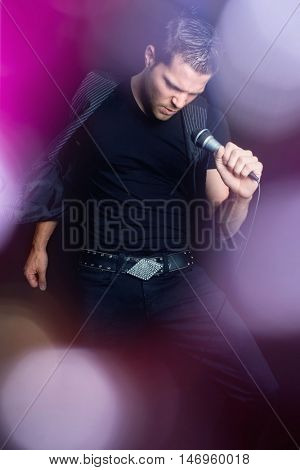 Sexy man singing into microphone