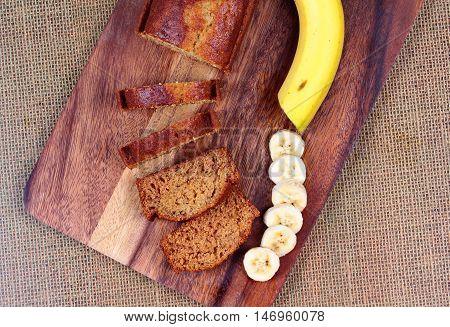 Homemade banana cake with sliced banana and whole banana on butcher served. Top view.
