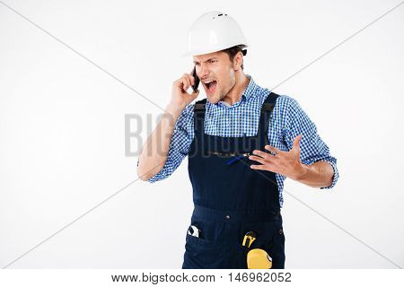 Angry screaming young builder talking on the phone isolated on a white background