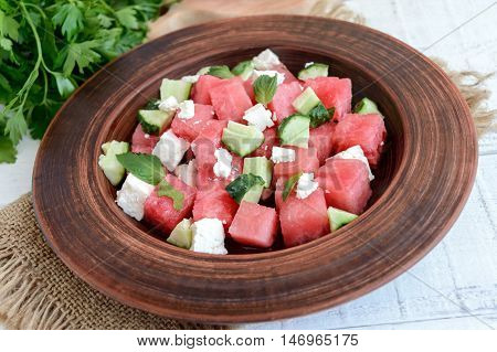 Light refreshing dietary gourmet salad with fresh watermelon cucumbers and feta cheese.