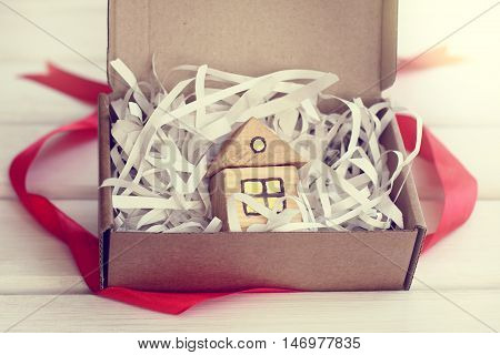 small toy symbol of the house in an open gift box / retro gift house
