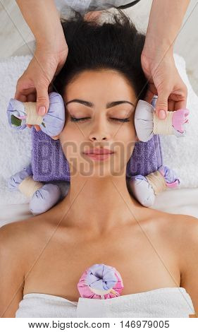 Herbal ball face massage in ayurveda spa. Female massagist with young woman in wellness center. Healthcare therapy to beautiful indian girl in beauty parlor, top view of face with eyes closed