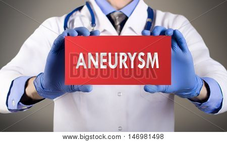 Doctor's hands in blue gloves shows the word aneurysm. Doctor in gloves on grey background. Medical concept.