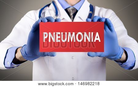 Doctor's hands in blue gloves shows the word pneumonia. Medical concept.