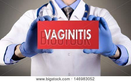 Doctor's hands in blue gloves shows the word vaginitis. Medical concept.
