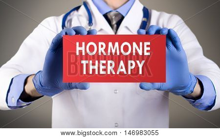 Doctor's hands in blue gloves shows the word hormone therapy. Medical concept.
