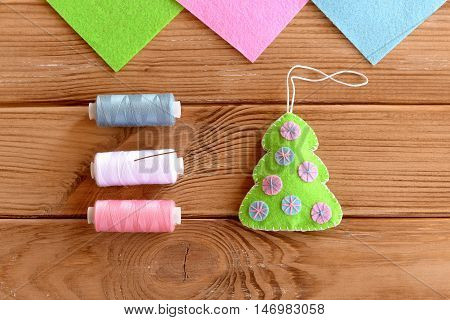 How to sew Christmas decoration. Step. Green felt Christmas tree embellishment, thread, needle on a wooden table. Hanging ornament Christmas tree. Simple and quick kids crafts. Top view