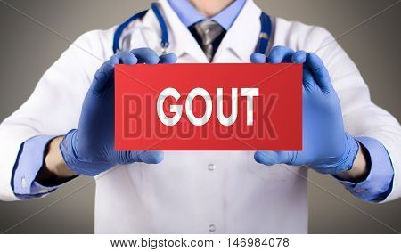 Doctor's hands in blue gloves shows the word gout. Medical concept.