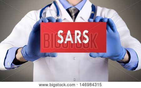 Doctor's hands in blue gloves shows the word sars. Medical concept.