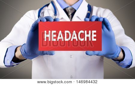 Doctor's hands in blue gloves shows the word headache. Medical concept.