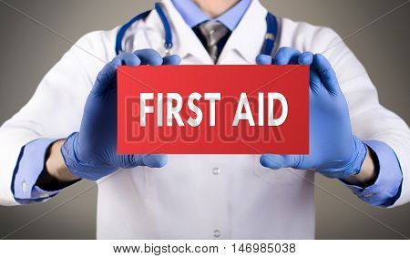 Doctor's hands in blue gloves shows the word first aid. Medical concept.