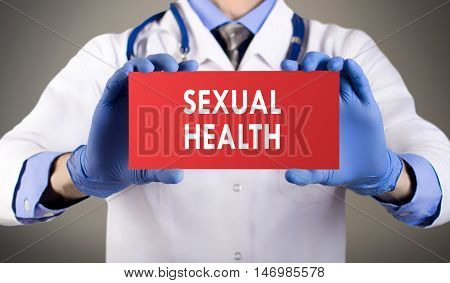 Doctor's hands in blue gloves shows the word sexual health. Medical concept.
